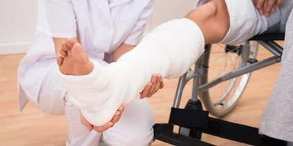 Close-up Of A Female Doctor Holding Disabled Patient's Leg